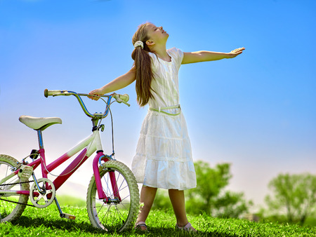 Bikes bicycling girl. Child girl wearing white skirt is pleased near to bicycle. Girl hands up. Blu sky and green tree on background. Summer park outdoor.