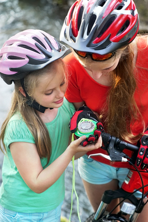 portrait orientation: Bikes cycling girl. Children girls rides bicycle. Girl in cycling look at compass. children looking for way . Stock Photo