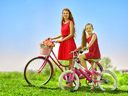 lunares rojos: Bicicletas chica bicicleta. Muchacha del adolescente y el uso de niños lunares rojos alineada que mira la cámara mantiene la bicicleta con flores canasta. verano al aire libre en el parque.