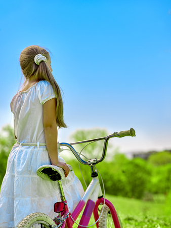 blu sky: Bikes bicycling girl. Child girl wearing white skirt  looks into the distance keeps  bicycle.  Blu sky and green tree on background. Summer park outdoor. Stock Photo