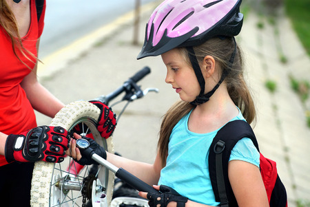 tire: Bikes bicyclist girl. Family wearing bicycle helmet  with hand pump for bicycle. Girl child pump up bicycle tire.  There are road and sidewalk at background.