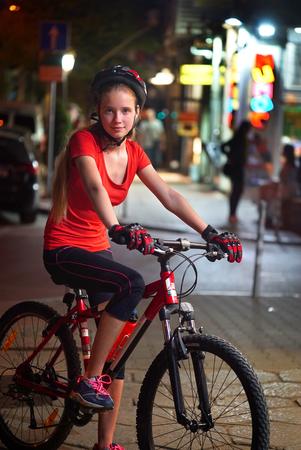 Bikes bicyclist girl. Girls wearing bicycle helmet. Night city street.