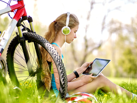 mobile headsets: Bikes cycling girl. Girl rides bicycle. Girl wearing headset in cycling watch in pc tablet near bicycle. Cycling is good for health. Cyclist looking pc tablet.