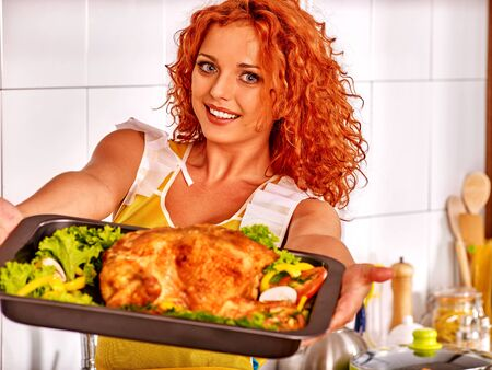 roast meat: Young woman cooking  chicken at kitchen. Woman offering a tray of chicken. Stock Photo