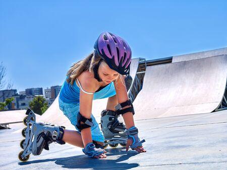 inline skater: Child Girl riding on roller skates in skatepark. Child is aganist blue sky.
