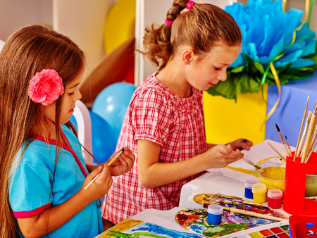 Group little children girls with brush painting on table in kindergarten . Children learn to painting. Stock Photo