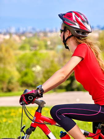 red sky: Bikes bicycling girl. Girl rides bicycle into city. Girl in cycling. Cycling is good for health. Cyclist is looking at city in distance. Travel by bicycle.