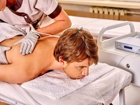 massage homme: Man recevant massage électrique au salon de beauté. soins de la peau de massage pour hommes. Esthéticienne portant des gants d'électricité. En arrière-plan est un appareil pour la cosmétologie matériel.