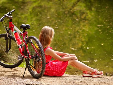 lunares rojos: Bicicletas bicicleta chica. Niñas el uso de lunares rojos visten paseos en bicicleta en el parque. La muchacha se sienta apoyado en bicicleta en la orilla. La bicicleta es el mejor tipo verano de ocio.