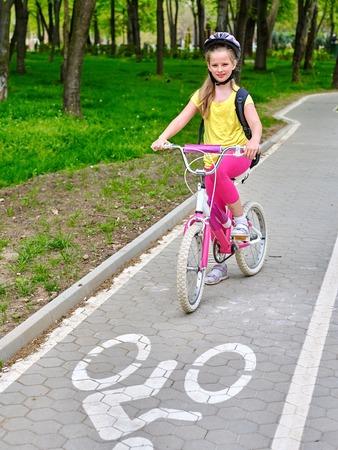 niños en bicicleta: Bicicletas ciclista chica. Chicas con casco de bicicleta con la bicicleta mochila ciclyng. muchachas de los niños en bicicleta en el carril bici amarilla. Bicicleta de los niños. Foto de archivo