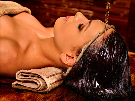 Young woman having pouring oil massage in India spa treatment. Shirodhara Pouring oil on head. Traditional India treatment.