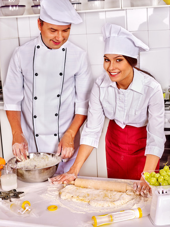 small cake: Happy woman and man in chef hat cooking dough  on professional kitchen. Small businesses. Stock Photo
