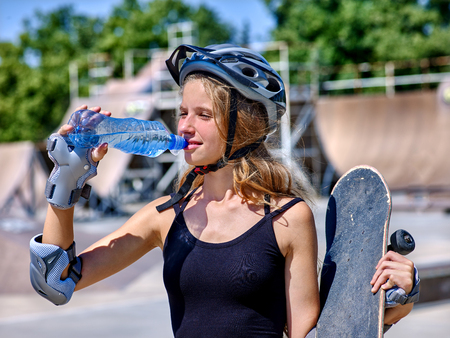 skateboarding tricks: Teen skateboarding his skateboard outdoor. Girl drink water and keeps skateboard. Stock Photo