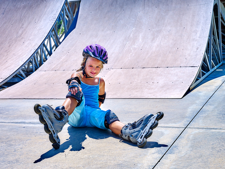 fall protection: Girl in roller skates sitting on ride in skatepark. girl in fall protection in skatepark.