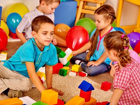 Group children game blocks on floor in kindergarten . Children play together. Stock Photo