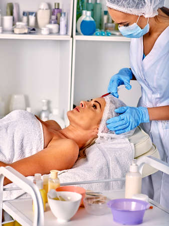 antiaging: Woman middle-aged in spa salon with beautician. Beauty woman giving botox injections. Anti-aging injection.