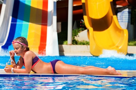 slide glass: Child on water slide at aquapark are drinking cold drinks. Child lie on edge of swimming pool. Child activities lifestyle. Summer holiday. Outdoor. Stock Photo