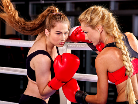 Two  women boxer wearing red  gloves to box in ring. Two  men boxer wearing helmet and  gloves boxing. Boxing is  extreme sport. Archivio Fotografico