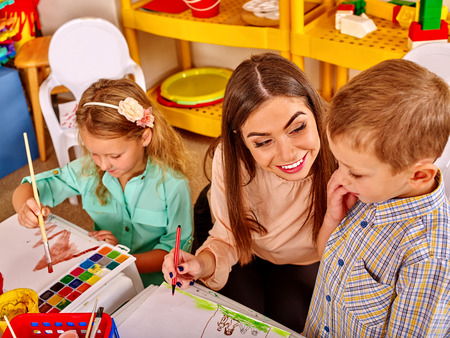 children painting: Children with teacher woman painting on paper at table  in  kindergarten . Learning children in start school. Stock Photo