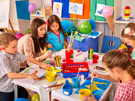 children painting: Children with teacher woman painting on paper at table  in  kindergarten . Children learn painting in start school.