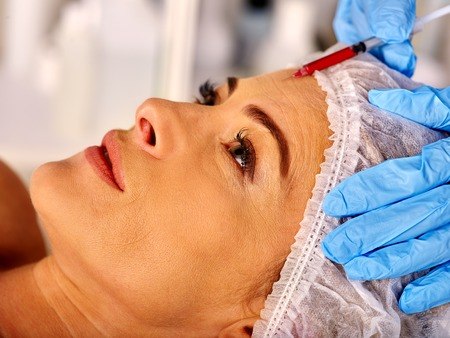 antiaging: Woman middle-aged in spa salon with beautician. Beauty woman giving anti-aging injections. Facial injections.