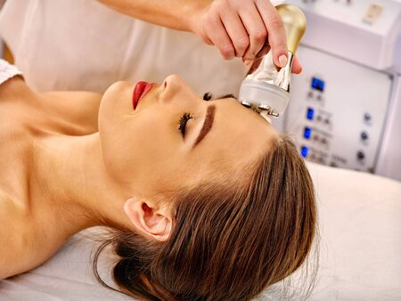 sound therapist: Close up of young woman receiving electroporation  facial therapy at beauty salon. Used for  therapy of multifunctional electroporation  device.