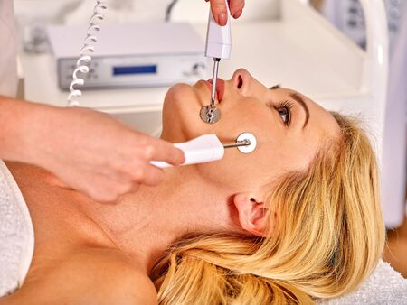 rf: Close up of  woman receiving electric facial eyes massage on microdermabrasion equipment at beauty salon. Used for  therapy of multifunctional electroporation  massage device.