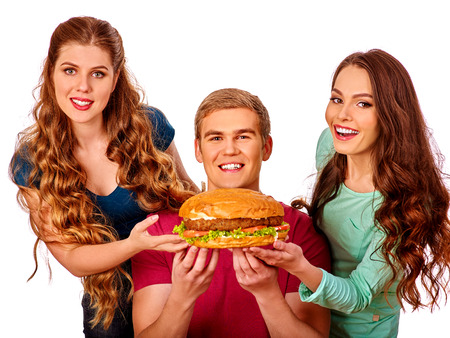 bite: Group people holding hamburgers . Fast food concept. Happy handsome man on foreground. Women feeding man fast food. Isolated. Stock Photo