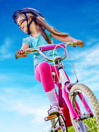 bicycling: Bikes bicycling child. Girl rides bicycle. Little girl in cycling. Cycling is good for child health. Cyclist look away. Bottom view. Stock Photo