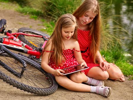 Bikes Radfahren Mädchen. Zwei Mädchen Schwestern tragen rote Tupfen Kleid Erholung in der Nähe von Fahrrad in Parks. Kinder beobachten Tablet PC. Mädchen im Ökotourismus. Standard-Bild