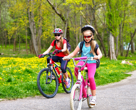 shared sharing: Bikes bicyclist girl. Girls wearing bicycle helmet  with rucksack ciclyng bicycle. Children outrace one another . Bike share program save money and time. Child in foreground  teenager on background.