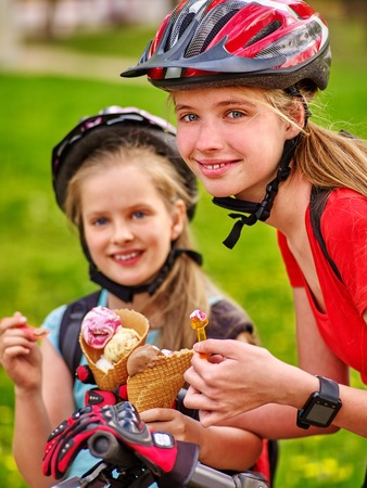 bicycling: Bikes bicyclist girl. Portrait of girls wearing bicycle helmet with rucksack rides bicycle. Girls children are bicycling in summer park. Happy girls biking eating ice cream cone .