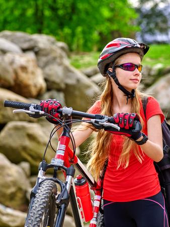 mountaineering: Bikes bicyclist girl. Girl rides bicycle into mountains. Girl on bicycle in mountaineering  . Mountaineering  is good for health. Cyclist looking away. Stock Photo