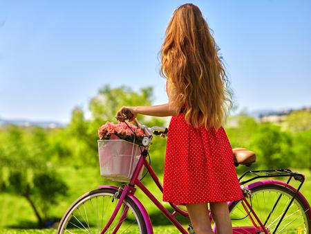 red polka dots: Bicicletas chica bicicleta. Chica con el pelo largo y rubio que llevaba lunares rojos alineada que mira en la distancia mantiene la bicicleta con flores canasta. Césped verde. Vista trasera. Foto de archivo