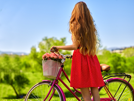 hair back: Bikes bicycle girl. Girl with long blond hair wearing red polka dots dress looking into distance keeps bicycle with flowers basket.  Green grass. Back view.