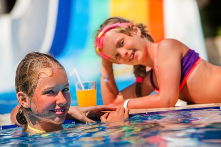 water   slide: Two children on water slide at aquapark lie on edge of swimming pool and drinking cold orange drink.  Children lie on edge of swimming pool. Summer holiday.Outdoor.
