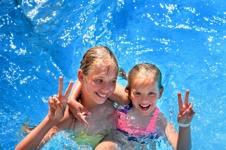 gesticulate: Two children in swimming pool . Children hugging and gesticulate hand victory sign.  Summer holiday.  Outdoor. Girl holding her sister in her arms. Children  activities lifestyle. Stock Photo
