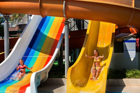 plummet: Two children on water slide at aquapark . Summer holiday. There are two water slides in aqua park. Children activities lifestyle. Children looking at camera. Outdoor. Stock Photo