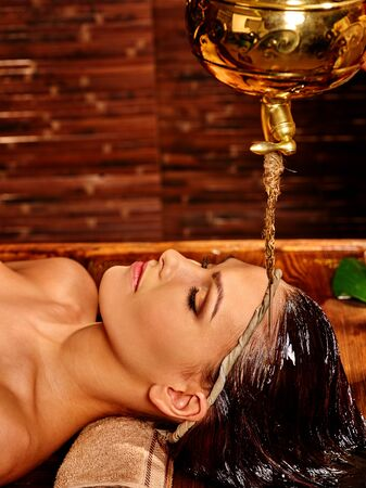 panchakarma: Young woman having pouring oil massage in India spa treatment. Shirodhara Pouring oil on head. Treatment of head.