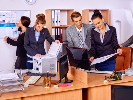 printing out: Happy group business people in office. Woman is printing out. Stock Photo