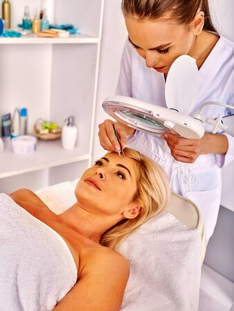tweezing: Woman middle-aged looks up in spa salon with young beautician. Tweezing eyebrow by beautician.