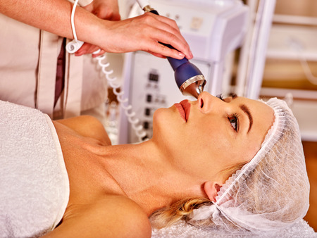 depressor: Young woman receiving electric ultrusound facial massage at beauty salon. Used for  therapy of multifunctional electroporation  device.