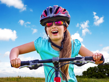 Bikes bicycling child. Girl rides bicycle. Girl wearing sport colored sunglasses. Cyclist look up.