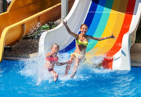 Two children on water slide at aquapark show thumb up. Summer swimming holiday. There are two water slides in aqua park. Swimming outdoor. Stock Photo