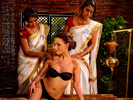 panchakarma: Woman having Ayurvedic spa massage treatment. Pouring oil. Spa massage with two person.