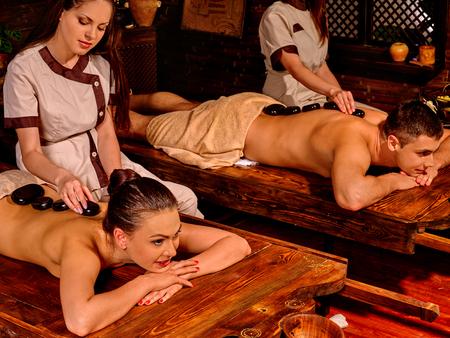 lastone: Young family having stone massage. Ayurveda lastone spa massage treatment. Stock Photo