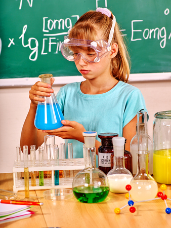 chemistry lesson: Child in mask holding flask in chemistry class. Chemistry lesson.