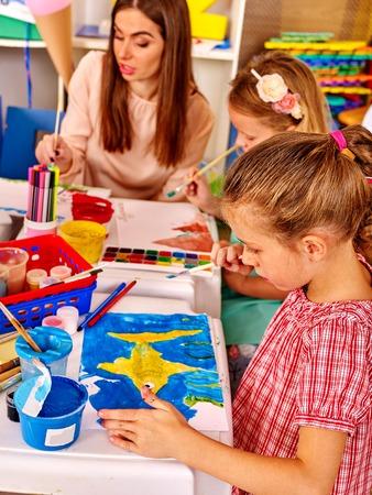 children painting: Children with teacher woman painting on paper at table in kindergarten . Teacher learn children.