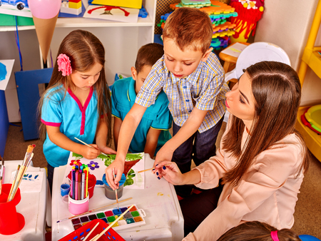 children painting: Children with teacher woman painting on paper at table in kindergarten .Teacher learn group of children. Stock Photo