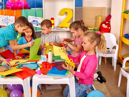 teach: Group kids holding colored paper on table in kindergarten .Children learn together in kindergarten.